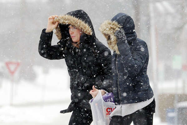Torri Varbero, left, and Ashley Graff, who both work in Old Greenwich, cross a snowy Sound Beach Avenue during the winter storm that hit Greenwich, Conn., Saturday , Jan. 23, 2016.