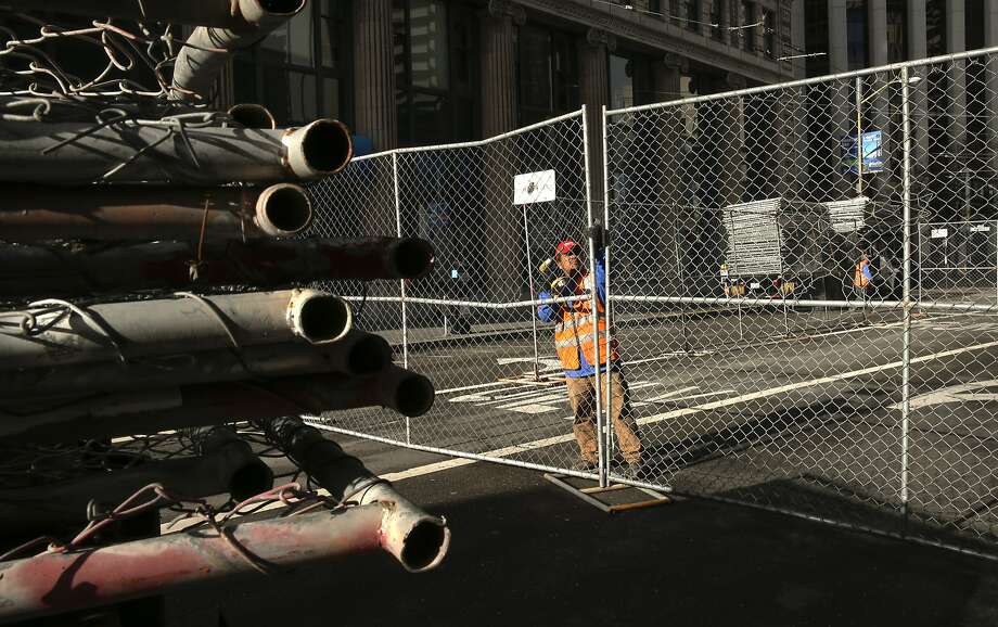 Arturo Ortega is part of a crews lining the blocks surrounding Superbowl City with portable fencing at the foot of Market St., on Sat. January 23, 2016, in San Francisco , Calif., as the city prepares for the big event. Photo: Michael Macor, The Chronicle