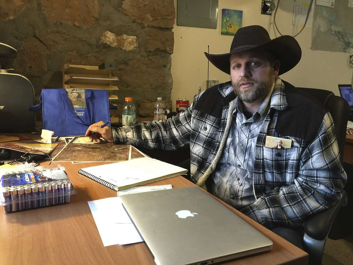 Ammon Bundy sits at a desk he's using at the Malheur National Wildlife Refuge in Oregon on Friday, Jan. 22, 2016. Bundy is the leader of an armed group occupying a national wildlife refuge to protest federal land policies. The leader of an armed group occupying the refuge met briefly with a federal agent Friday, but left because the agent wouldn't talk with him in front of the media. (AP Photo/Keith Ridler)