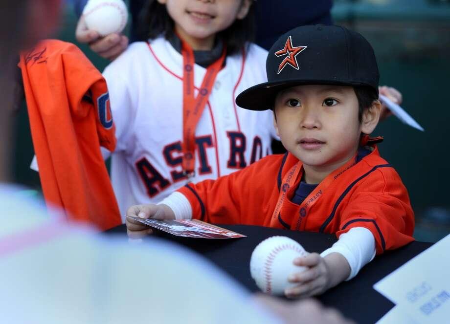 Daisuke Nakamura, 4, hands a baseball to Houston Astros catcher Max Stassi (12) for an autograph at Astros fan fest at Minute Maid Park Saturday, Jan. 23, 2016, in Houston. ( Jon Shapley / Houston Chronicle ) Photo: Houston Chronicle