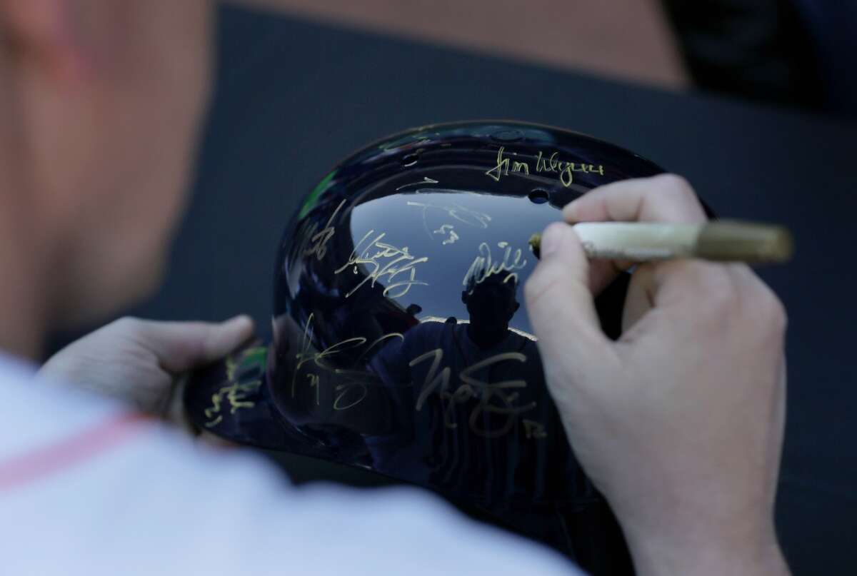 Houston Astros pitcher Will Harris (36) signs a helmet for David Torres at Astros fan fest at Minute Maid Park Saturday, Jan. 23, 2016, in Houston. Torres has been a season ticket holder for 20 years, including the two years he spent in Afghanistan. ( Jon Shapley / Houston Chronicle )