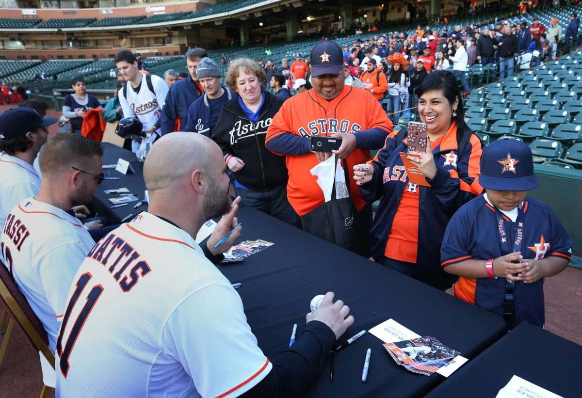 Monica Mendez, second from right, smiles as she takes a picture of Houston Astros designated hitter Evan Gattis (11) at Astros fan fest at Minute Maid Park Saturday, Jan. 23, 2016, in Houston. Mendez came with her husband Manuel, third from right, and son Manuel, Jr., right. ( Jon Shapley / Houston Chronicle )