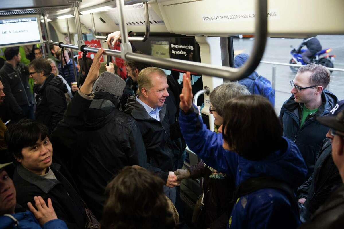 Seattle Mayor Ed Murray shakes hands with passengers.