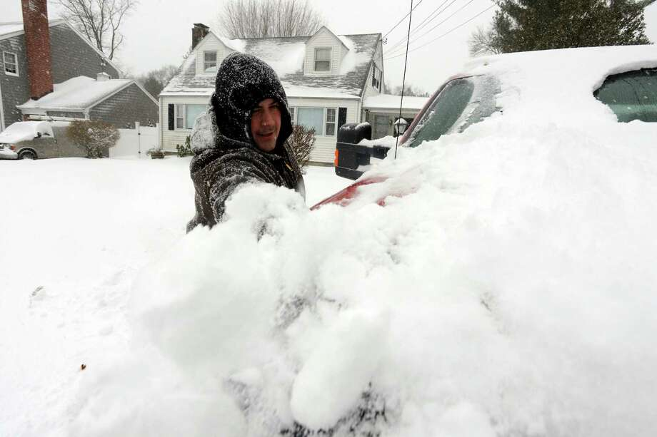 Andrew Kapusta clears snow from his truck at his Unity Road home as he gets ready to venture out in Stamford, Conn. during a winter storm on Saturday, Jan. 23, 2016. Photo: Matthew Brown / Hearst Connecticut Media / Stamford Advocate