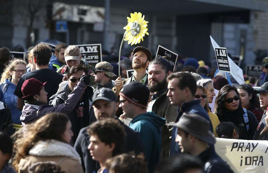 Mark Van Loan of Redding carries a silk sunflower as antiabortion activists walk down Market Street during the S.F. March for Life. Photo: Paul Chinn, The Chronicle