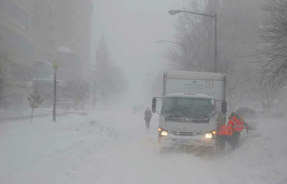 As the snow blows, a crew works to free a truck stuck in the snow, Saturday, Jan. 23, 2016 in Washington. A blizzard with hurricane-force winds brought much of the East Coast to a standstill Saturday, dumping as much as 3 feet of snow, stranding tens of thousands of travelers and shutting down the nation's capital and its largest city. Photo: Alex Brandon, AP / AP