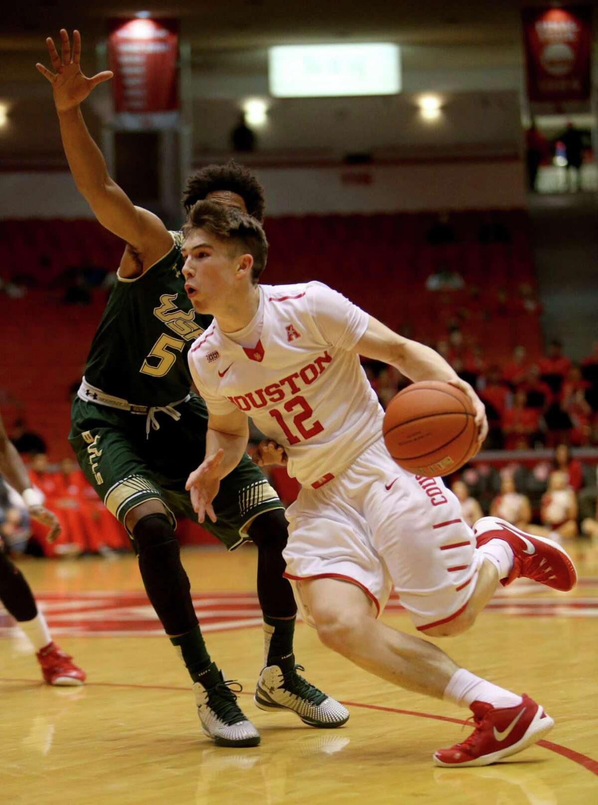 Houston Cougars guard Wes VanBeck (12) drives to the basket guarded by South Florida Bulls guard Nehemias Morillo (5) during the second half at Hofheinz Pavilion on the campus of the University of Houston Saturday, Jan. 23, 2016, in Houston, Texas. Houston lost 62-71.
