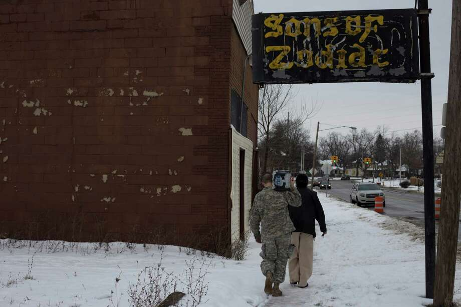 FILE N A Michigan National Guardsman helps a resident carry bottled water to her car at a fire station in Flint, Mich., Jan. 15, 2016. At every major decision point over more than a year, officials at all levels of government acted in ways that contributed to FlintOs tainted water crisis and allowed the public health emergency to persist for months. (Brittany Greeson/The New York Times) ORG XMIT: XNYT62 Photo: BRITTANY GREESON / NYTNS
