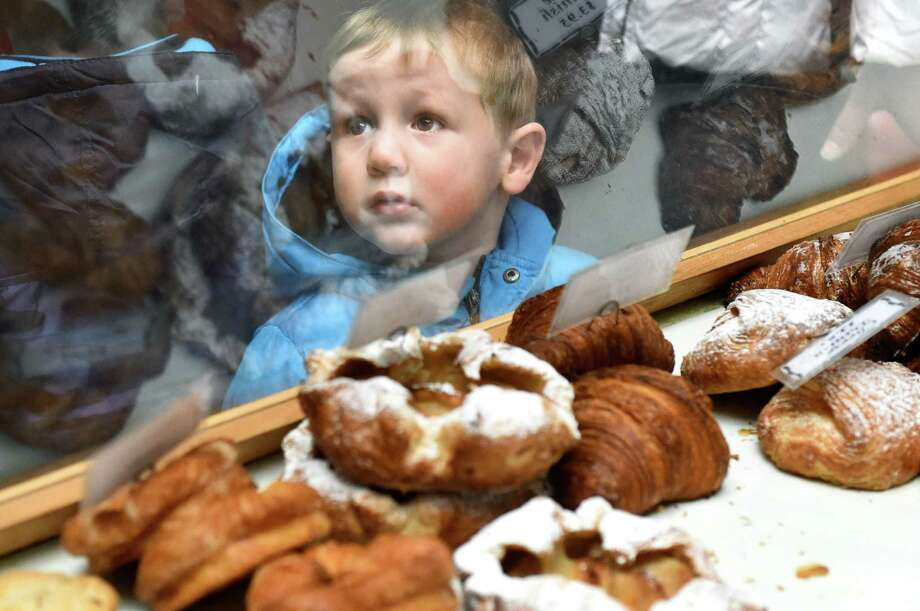 Simon Holler, 2, of Schenectady looks through the glass case at pastries in the Mrs. London's Bakery booth during the Saratoga Farmers Market on Saturday, Jan. 23, 2016, at the Lincoln Baths in Saratoga Springs, N.Y. (Cindy Schultz / Times Union) Photo: Cindy Schultz / 10034817A
