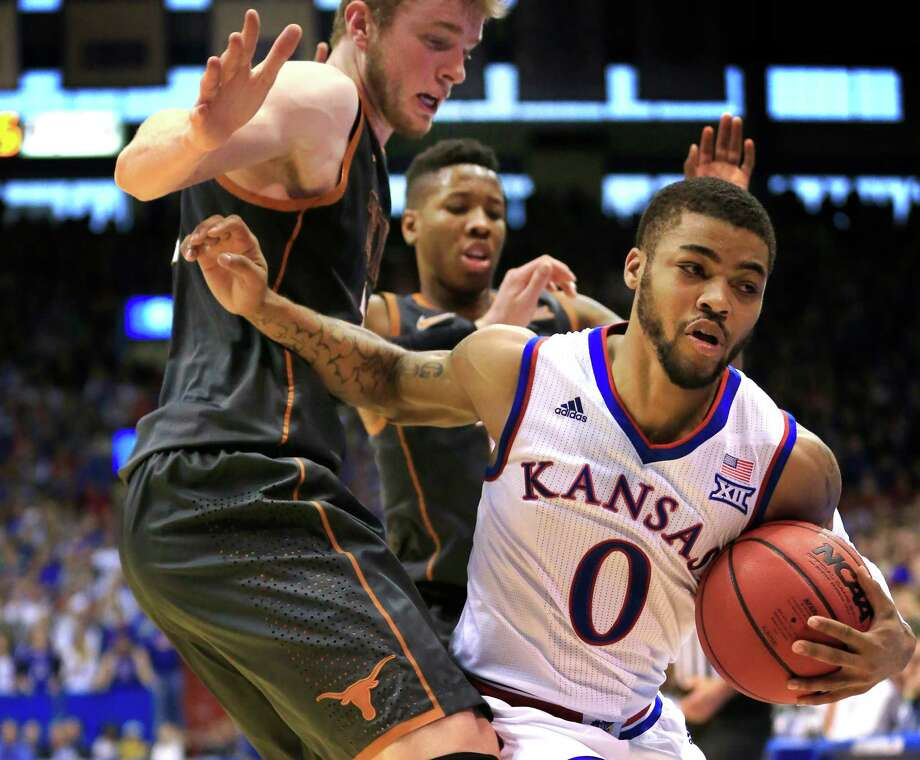 Kansas guard Frank Mason III (0) calls timeout while trapped by Texas forward Connor Lammert, left, during the second half of an NCAA college basketball game in Lawrence, Kan., Saturday, Jan. 23, 2016. Kansas defeated Texas 76-67. (AP Photo/Orlin Wagner) Photo: Orlin Wagner, STF / Associated Press / AP