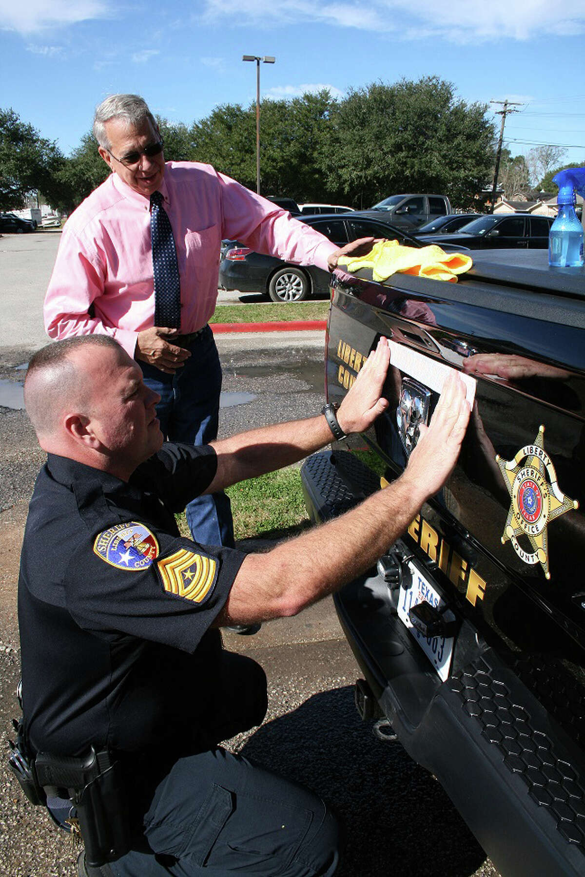 """Sheriff Bobby Rader, top, looks on as Sgt. Brett Audilet places the first decal on a patrol unit. Some of the Texas law enforcement agencies started putting é¢Ã©""""éºIn God We Trusté¢Ã©""""é¹ decals on their patrol vehicles and it seems to be a growing movement across the country that citizens of Liberty County will soon be seeing as well."""