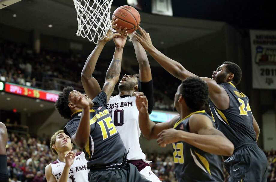 Texas A&M's Tonny Trocha-Morelos (10) fights fir a rebound against Missouri's Wes Clark (15) and Kevin Puryear (24) during the first half of an NCAA college basketball game, Saturday, Jan. 23, 2016, in College Station, Texas. (AP Photo/Sam Craft) Photo: Sam Craft, FRE / Associated Press / FR 145148 AP