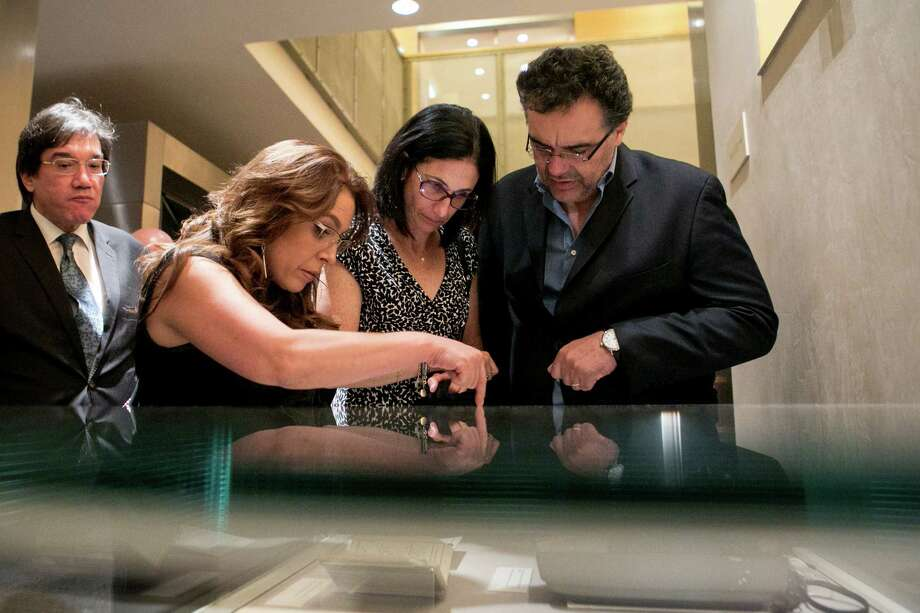 Journalist Fernanda Familiar, left, and Adriana Sheinbaum, center,  wife of Rodrigo Garci­a, right, the son of Gabriel Garci­a Marquez, look at a display of items from the Garcia Marquez archive at the Harry Ransom Center in 2015. The library has just acquired about 180 books from the Colombian writer's personal library. Photo: Ilana Panich-Linsman / 546621