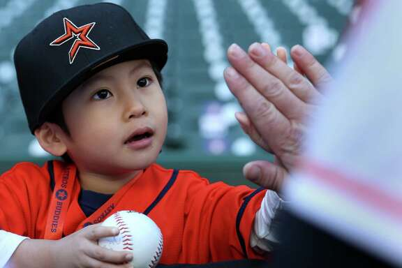 Daisuke Nakamura, 4, gets a high-five from Evan Gattis while the Astros designated hitter mingled with fans, posed for photographs and autographed items at Minute Maid Park during Saturday's Astros FanFest.