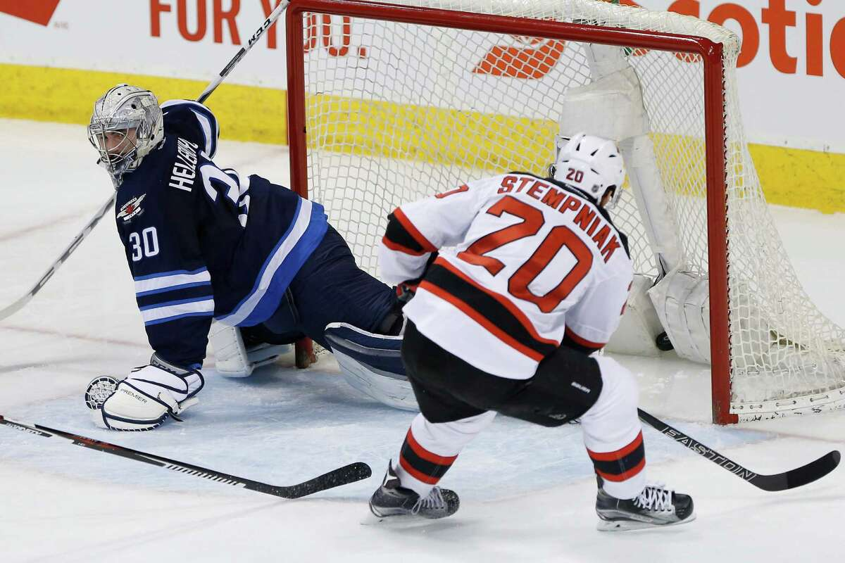 New Jersey Devils' Lee Stempniak (20) scores on Winnipeg Jets goaltender Connor Hellebuyck (30) during the first period of an NHL hockey game Saturday, Jan. 23, 2016, in Winnipeg, Manitoba. (John Woods/The Canadian Press via AP) ORG XMIT: JGW103