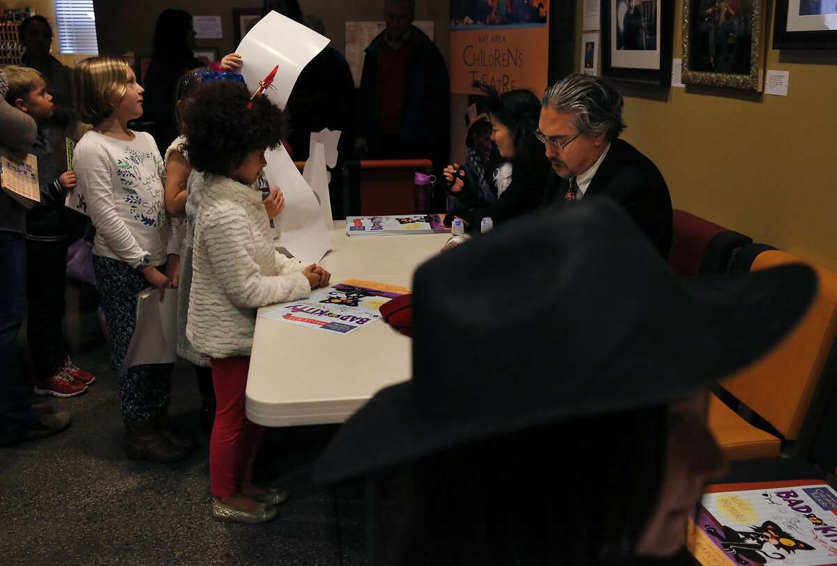 Dasia Norcome, 8, left center, watches as author Nick Bruel signs her book while Sango Tajima (Kitty) signs posters as friend Aveline Heryer, 8, waits in the foreground after the Bay Area Children's Theatre's production of Bad Kitty based on stories by Bruel Jan. 23, 2016 in Berkeley, Calif.