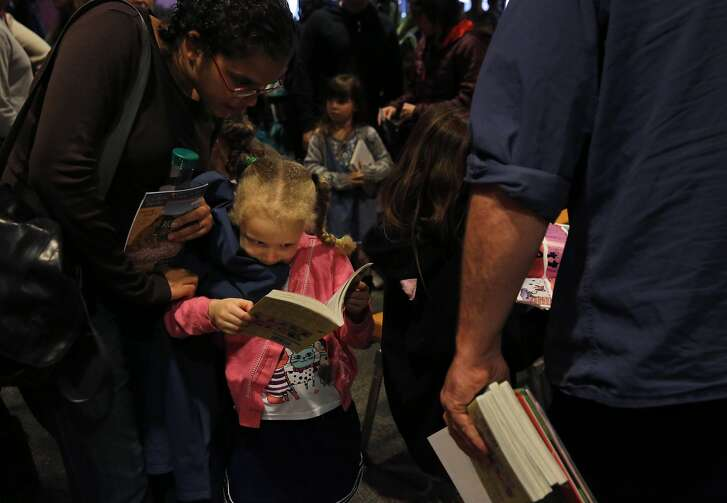 Ella Alexis, 4, looks at her Bad Kitty book with her mom Aldona Clottey as they wait in line to get it signed by the author Nick Bruel after they watched the Bay Area Children's Theatre's production of Bad Kitty based on stories by Bruel Jan. 23, 2016 in Berkeley, Calif.