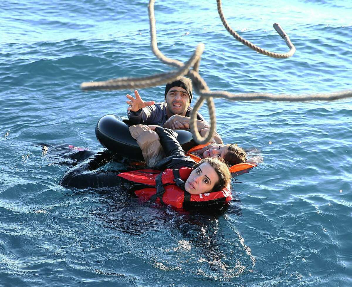 Turkish Coast Guard personnel throw a rope toward refugees as they swim with buoys, after they toppled over a fishermen dinghy en route to Greece on January 22, 2016 in Didim district of Aydin, Turkey. 4 refugees body including 3 children pulled out of the water as Turkish coast guard personnel rescued 43 others. (Photo by Emin Menguarslan/Anadolu Agency/Getty Images)