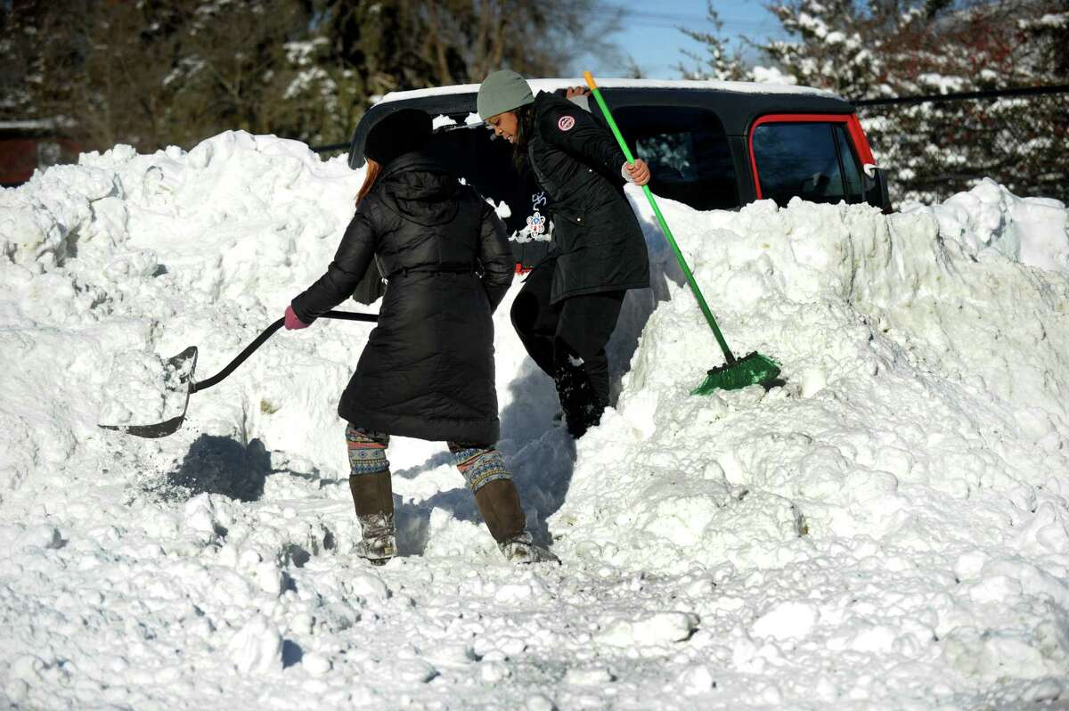 Victoria Cipri, left, helps her friend Shirley Rodriguez, dig her Jeep out after snowplows buried the car in the parking lot of Park Avenue School in Danbury, Sunday morning, January 24, 2016.