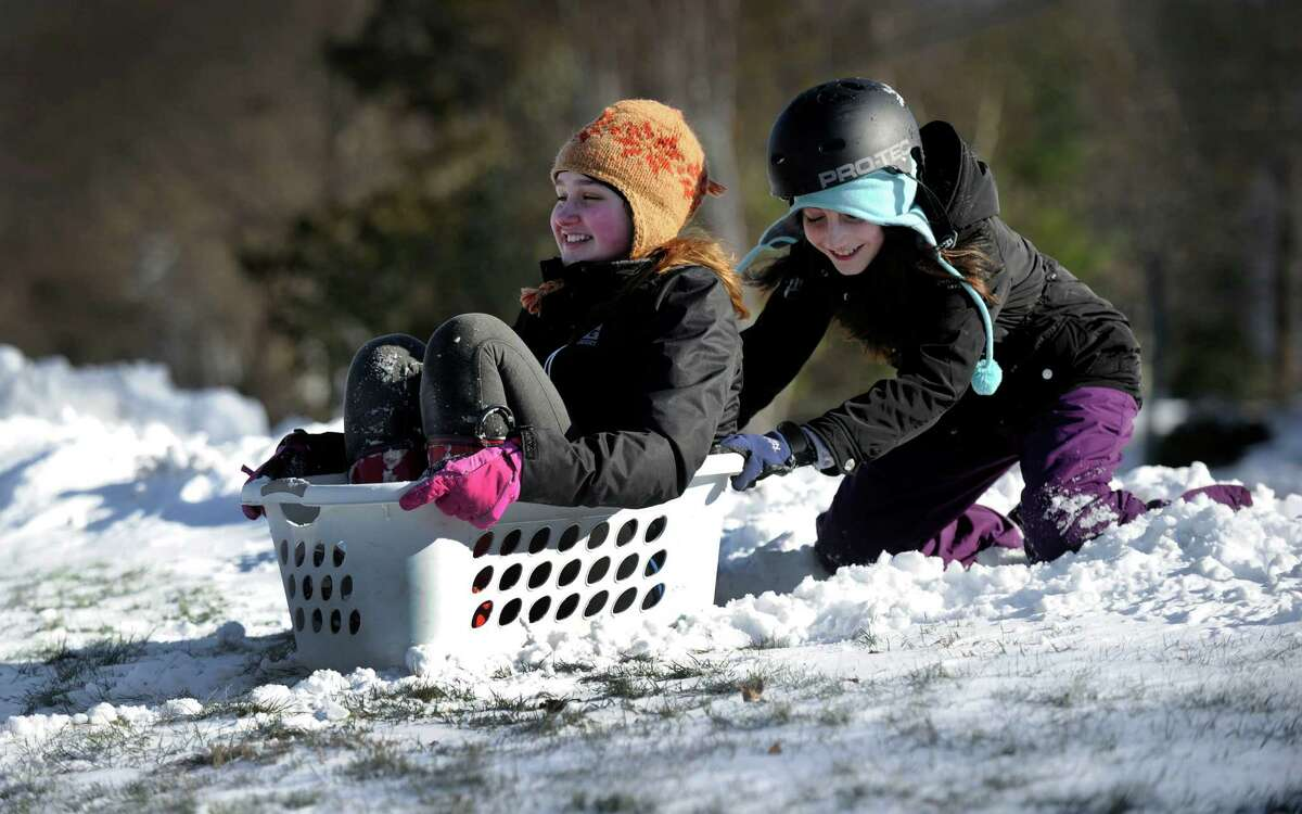 Playing in the snow, friends Allyson Norkowski, 13, left, and Rachel Kalmus, 12, use a laundry basket as a sled - with limited success at Candlewood Shores in Brookfield Sunday, January 24, 2016.