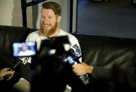 Sean Doolittle, pitcher, talks to several reporters before A's Fanfest at the Coliseum in Oakland, California, on Sunday, Jan. 24, 2016.