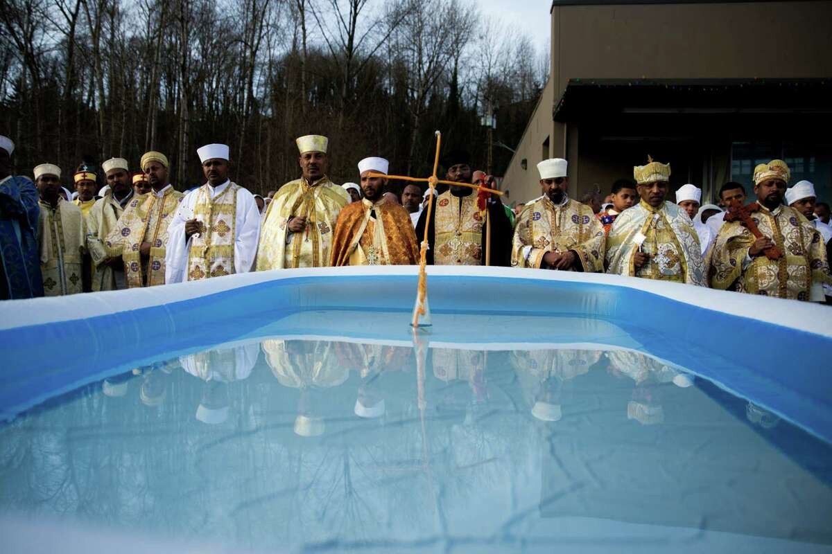 Ethiopian Orthodox Tewahedo Church priests and monks prepare to bless the water that will be sprinkled on the heads of their followers during Timkat, (Epiphany), at King's Hall on Sunday, Jan. 24, 2016.