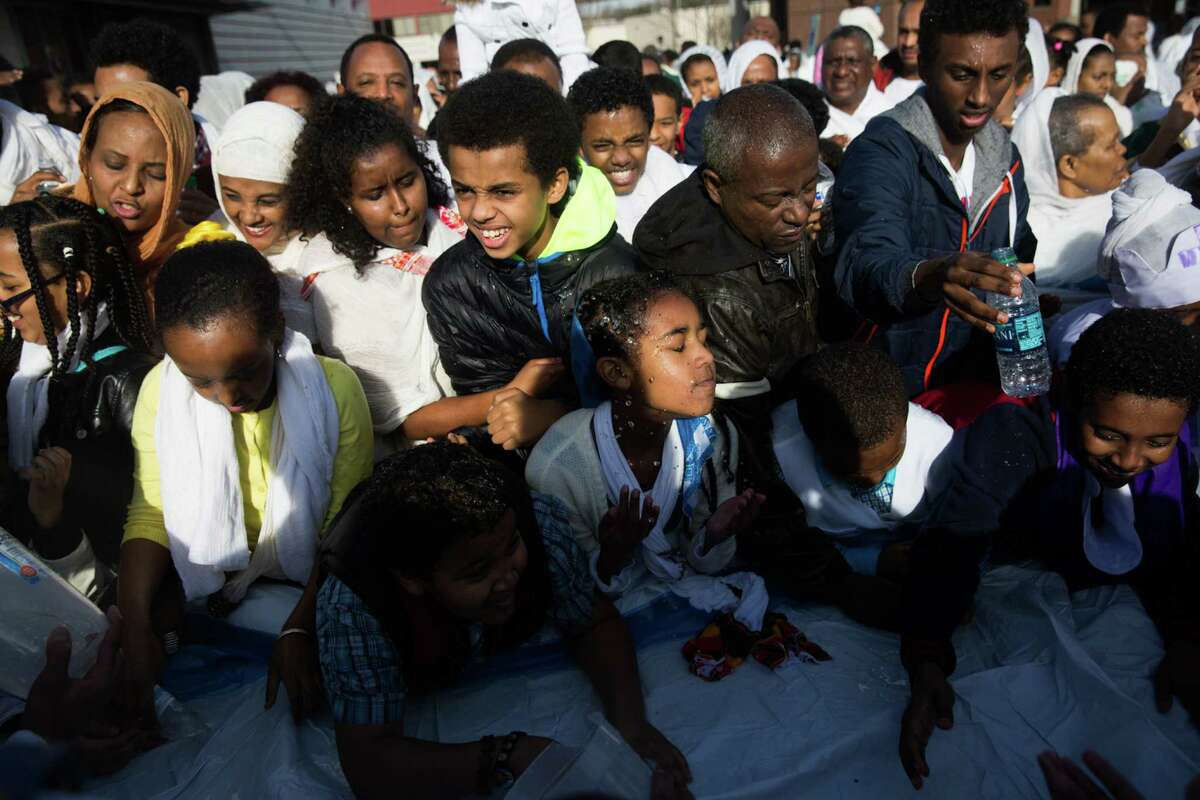 Men, women and children of the Ethiopian Orthodox Tewahedo Church splash holy water on themselves and their neighbors during Timkat, (Epiphany), at King's Hall on Sunday, Jan. 24, 2016.
