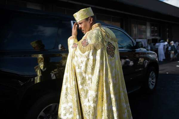 An Ethiopian Orthodox Tewahedo Church priest gets in his church's car following the celebration of Timkat, (Epiphany), at King's Hall on Sunday, Jan. 24, 2016.