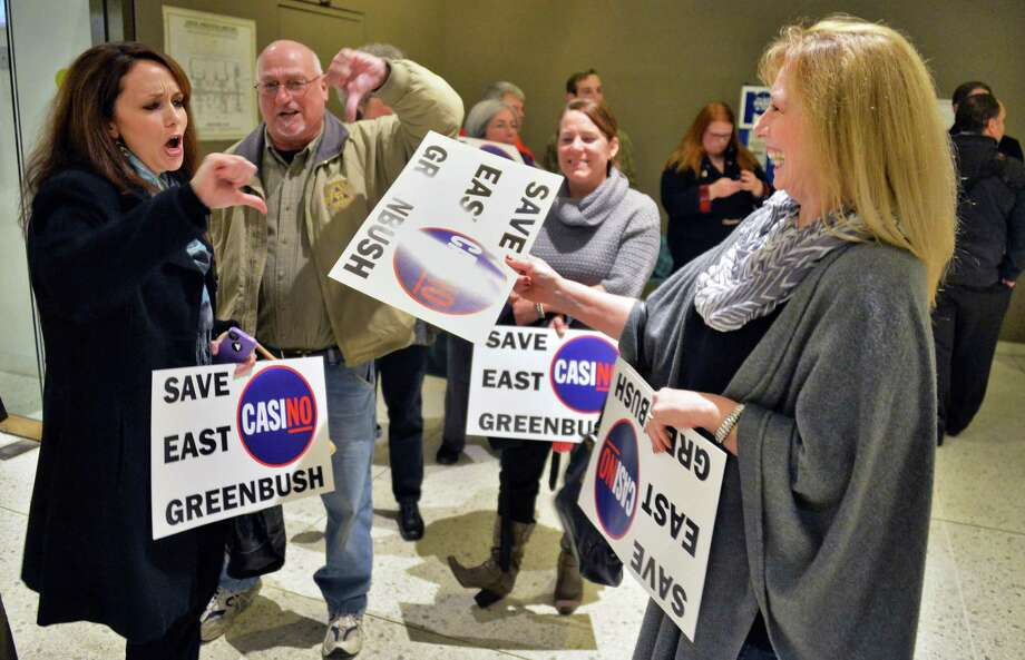 Tina Tierney, left, takes signs from Jennifer Jenkins, right, as opponents of the East Greenbush casino site wait in line for the beginning of the New York Gaming Facility Location Board's  meeting Wednesday Dec. 17, 2014, in Albany, NY.  Tierney is now on the East Greenbush town board, and recently voted to rescind the town's support for a casino. (John Carl D'Annibale / Times Union) Photo: John Carl D'Annibale / 00029888A