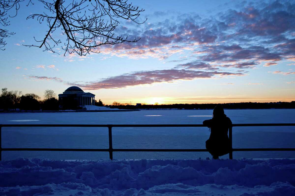 Courtney Miller, a student at American University, from Fort Montgomery, N.Y., sits on the railing of the Tidal Basin as she watches the sunset behind the Jefferson Memorial, Sunday, Jan. 24, 2016 in Washington. Brilliant sunshine and gently rising temperatures followed the mammoth blizzard that paralyzed Washington and set a single-day snowfall record in New York City, enabling millions to dig out Sunday and enjoy the winter.