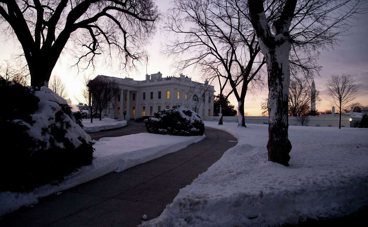 The White House grounds are blanketed in snow in Washington, early Monday, Jan. 25, 2016. East Coast residents who made the most of a paralyzing weekend blizzard face fresh challenges as the workweek begins: slippery roads, spotty transit service mounds of snow, and closed schools and government offices.