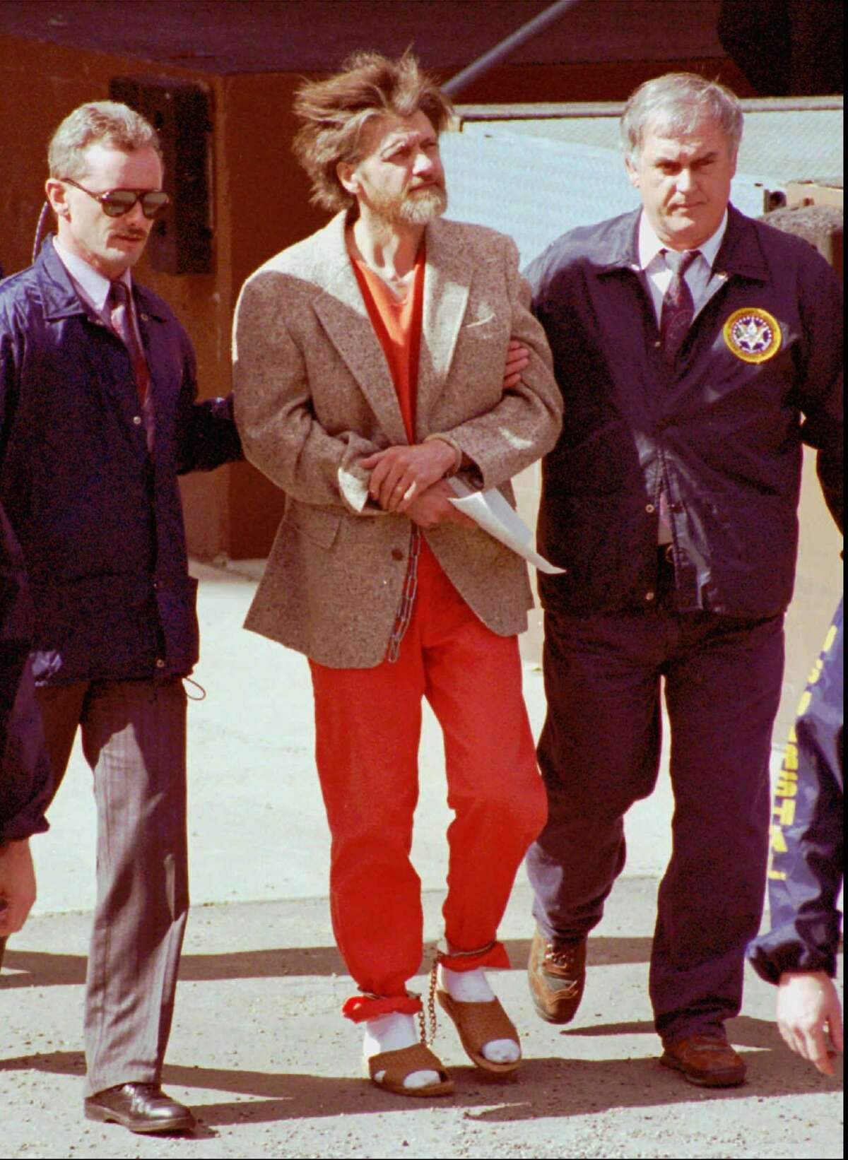 Federal agents escort Unabomber suspect Theodore Kaczynski as they leave the federal courthouse in Helena, Mont., on April 4, 1996. Kaczynski has agreed to plead guilty in return for a sentence of life in prison without parole, a federal official said Thursday, Jan. 22, 1998. (AP Photo/John Youngbear)