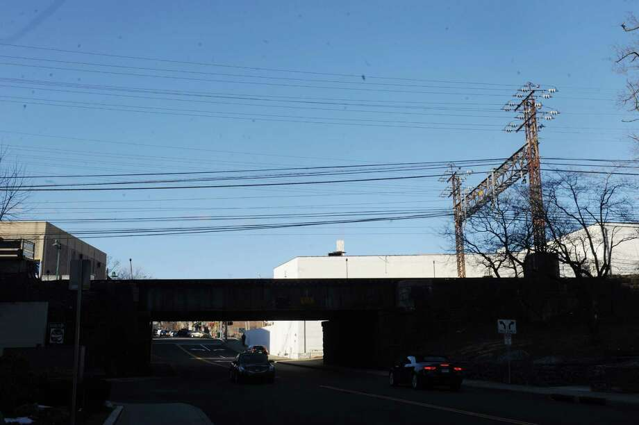 Power lines, like ones seen on Railroad Avenue over the Metro North tracks, are being looked at by an Eversource helicopter taking photos on Monday.. Photo: Helen Neafsey / Helen Neafsey / Greenwich Time