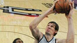 San Antonio Spurs' Boban Marjanovic shoots over Dallas Mavericks' Jeremy Evans during second half action Sunday Jan. 17, 2016 at the AT&T Center. The Spurs won 112-83.