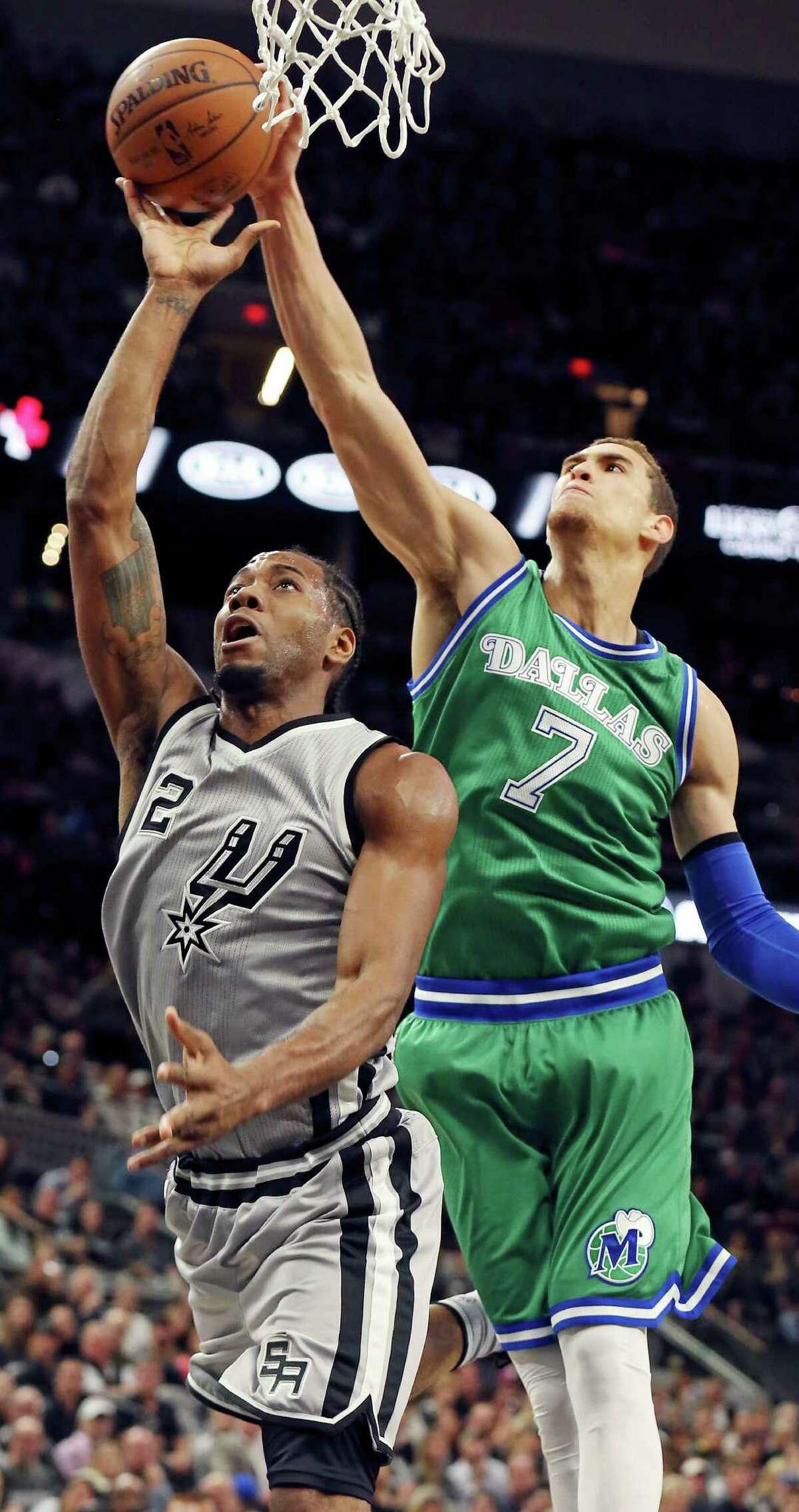 San Antonio Spurs' Kawhi Leonard shoots around Dallas Mavericks' Dwight Powell during first half action Sunday Jan. 17, 2016 at the AT&T Center.