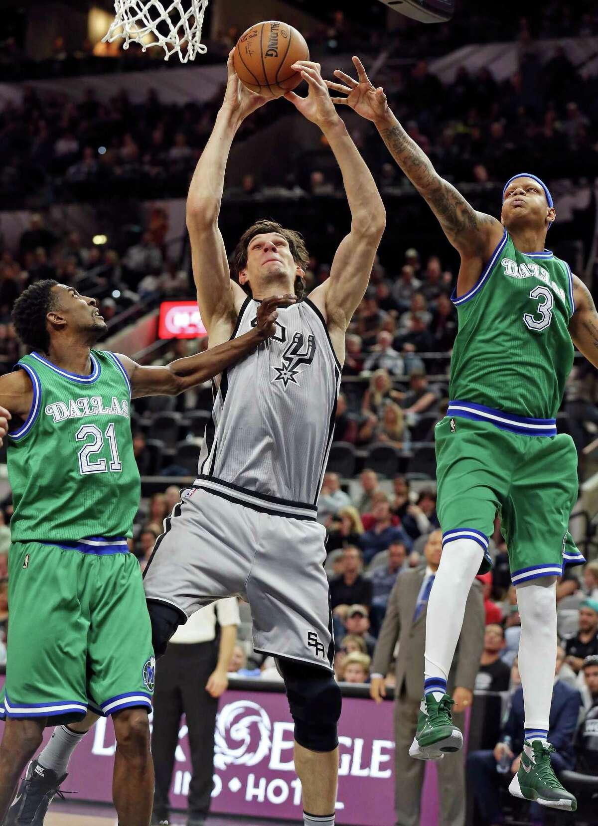 San Antonio Spurs' Boban Marjanovic grabs for a rebound between Dallas Mavericks' Jeremy Evans (left) and Charlie Villanueva during second half action Sunday Jan. 17, 2016 at the AT&T Center. The Spurs won 112-83.