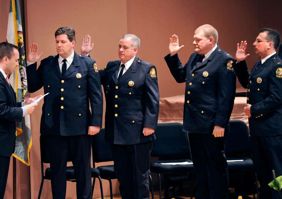 Greenwich First Selectman Peter Tesei, far left, swears in four new Greenwich Police Department captains during a ceremony in the Cole Auditorium at Greenwich Library on March 26th. The new captains are, from left, Timothy Berry, James Heavey, Mark Kordick and Mark Marino. Photo: File Photo / Greenwich Time File Photo