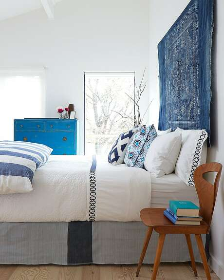 Sonoma farmhouse with an update by Allison Bloom: In the bedroom, a vintage Hmong batik textile serves as a l headboard. A bright blue flea market dresser pairs with a French antique dining chair.  Photo: John Merkl
