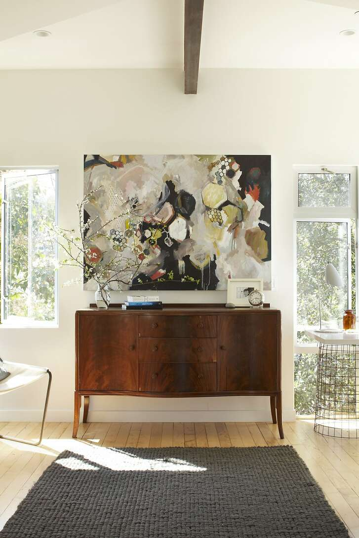 Bloom House Ð  Bureau with art: A vintage French bureau is mixed with modern abstract art Ð wire metal baskets form an airy base for a desk. The combination of modern, clean lines, pre-war bureau and abstract art create a boho mashup that feels light and warm.  Credit: John Merkl