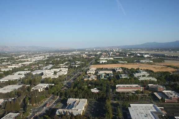 North First Street, center of photo, is a main artery from downtown San Jose to the northern city, and includes light rail access. San Jose Mineta International Airport is seen on the right. Part of the open field, center, is among Apple's purchased lands in North San Jose. The area has easy access to the airport, hotels, universities, and transit options.