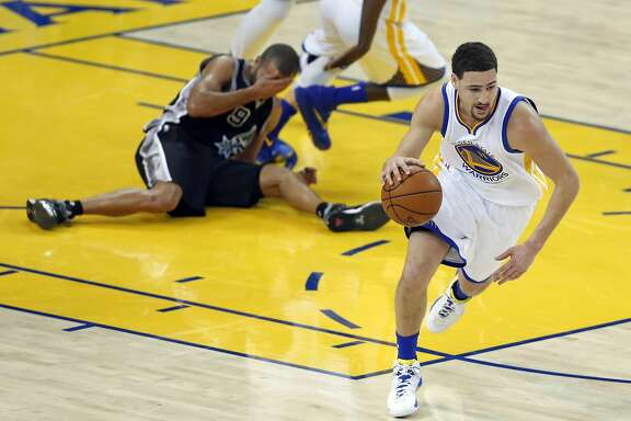 Golden State Warriors' Klay Thompson heads up court as San Antonio Spurs' Tony Parker reacts to being hit in the nose in 2nd quarter during NBA game at Oracle Arena in Oakland , Calif., on Monday, January 25, 2016.