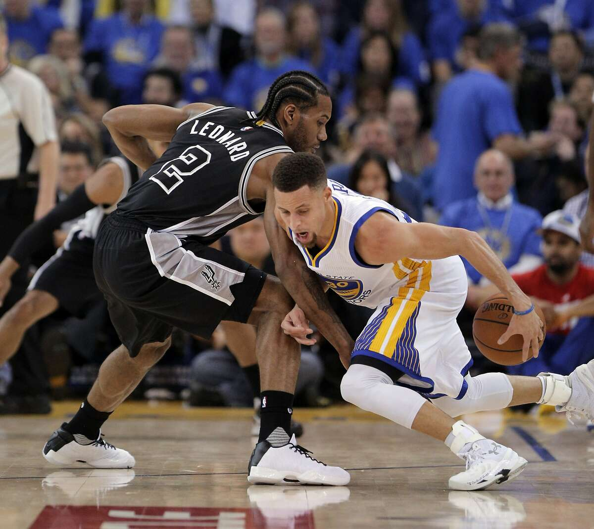 Stephen Curry (30) dribbles around Kawhi Leonard (2) during the first half of the Golden State Warriors game against the San Antonio Spurs at Oracle Arena in Oakland, Calif., on Monday, January 25, 2016.