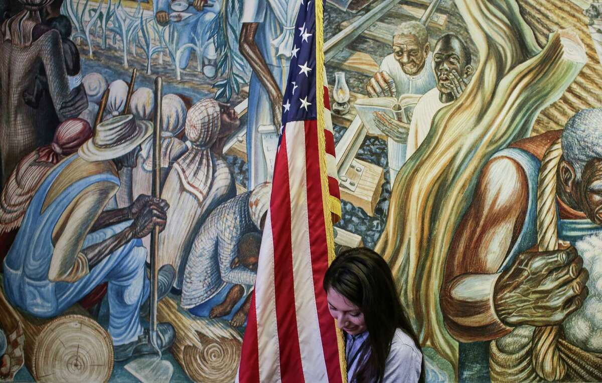 Congresswoman Sheila Jackson Lee's intern, Patricia Sepulveda, moves a flag in front of the mural, the Contribution of Negro Women to American Life and Education, after a press conference with members of the Board of the Blue Triangle Multi-Cultural Association Monday, Jan. 25, 2016, in Houston to discuss a leaky roof that threatens the historic mural by John Biggers.
