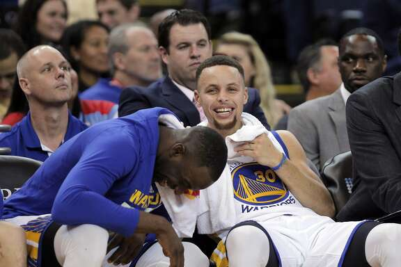 Draymond Green (23) and Stephen Curry (30) laugh on the bench  during the second half of the Golden State Warriors game against the San Antonio Spurs at Oracle Arena in Oakland, Calif., on Monday, January 25, 2016.
