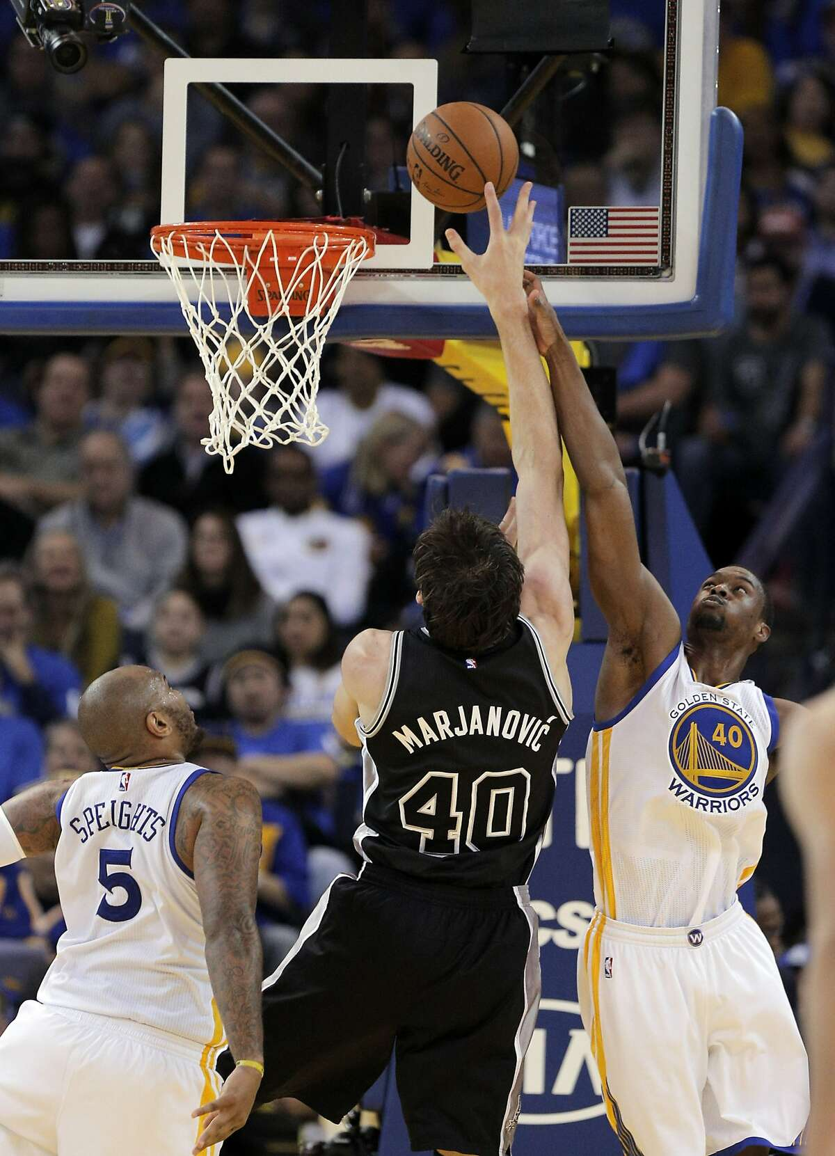 Harrison Barnes (40) and Marreese Speights (5) defend againt a shot by Boban Marjanovic (40) during the second half of the Golden State Warriors game against the San Antonio Spurs at Oracle Arena in Oakland, Calif., on Monday, January 25, 2016.