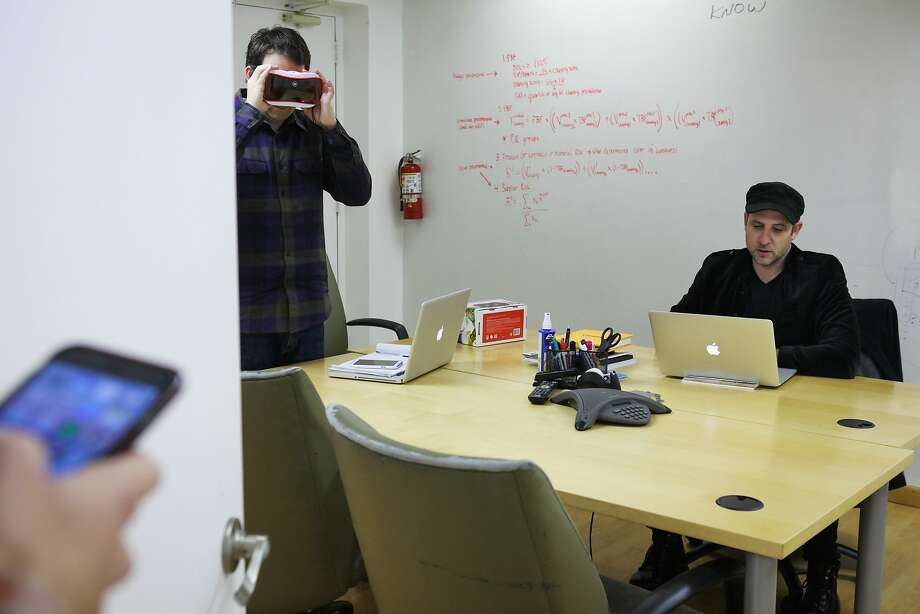 Justin Dillon (right), founder of Made in a Free World, works at his desk while Ben Hafner (left) tries out a virtual reality headset,  in San Francisco, California on Friday, January 22, 2016. Photo: Gabrielle Lurie, Special To The Chronicle