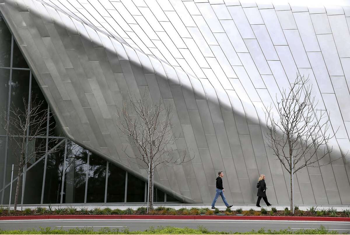 People walk past the exterior steel skin of the film theater at the new location of the Berkeley Art Museum and Pacific Film Archive in Berkeley, Calif. on Tuesday, Jan. 26, 2016. BAMPFA reopens to the public on Sunday.