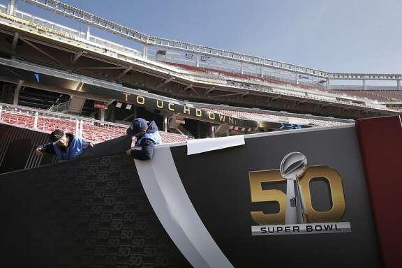 Nick Fondacaro, (left) and Ignacio Vegas install graphics as preparations for Super Bowl 50 continue at Levi's Stadium on Tues. January 26, 2016, in Santa Clara, Calif.,
