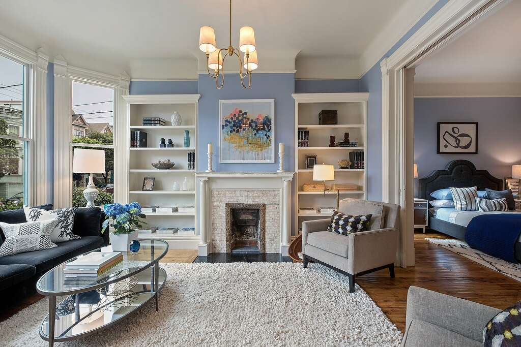 The Formal Living Room Hosts A Decorative Fireplace Built In Shelving Large Windows