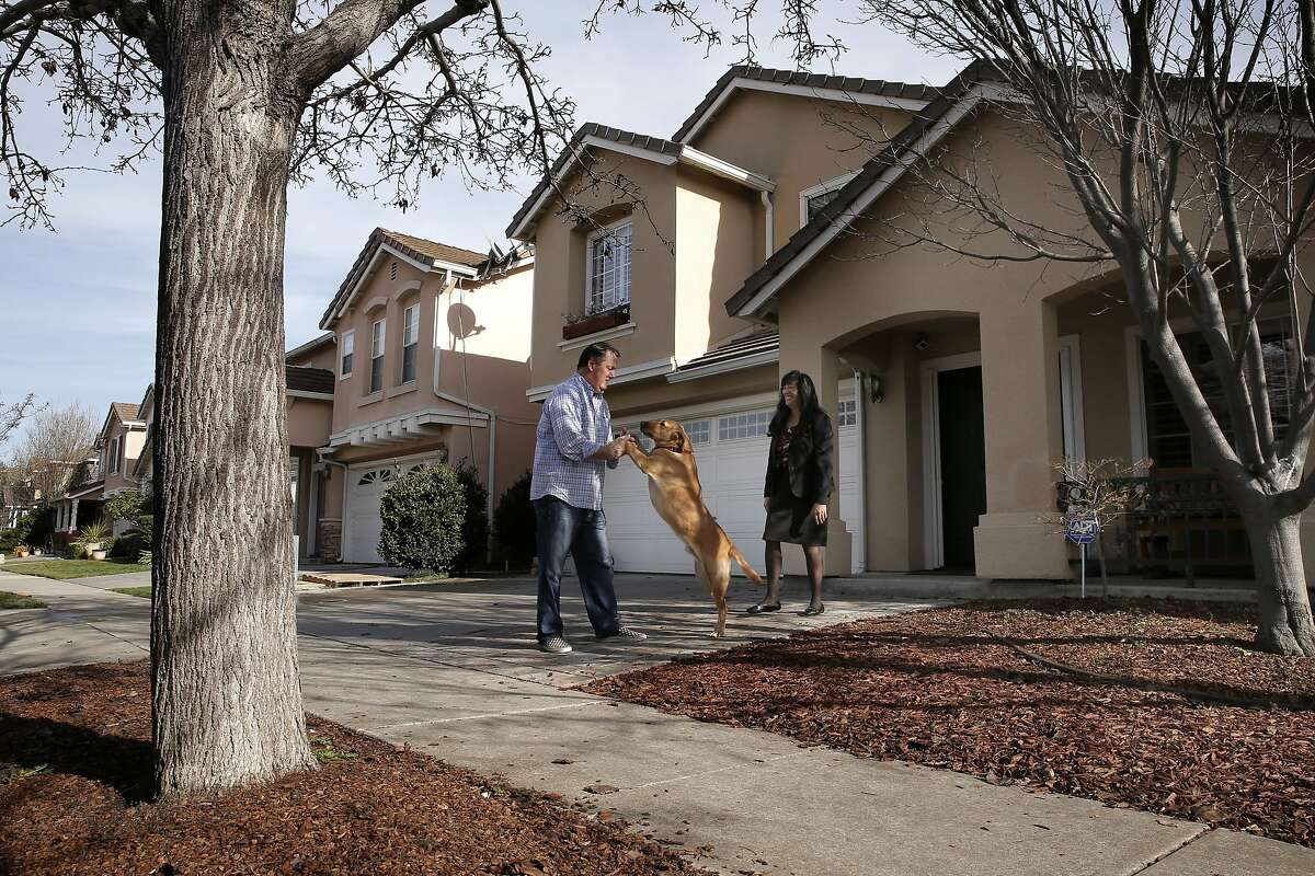 Tom and his partner Kim Lain and their dog Beau in front of their home, in San Jose, Calif, on Tues. January 26, 2016. With a short walk to Levi's Stadium they are hoping to rent out their home to fans for Super Bowl 50.